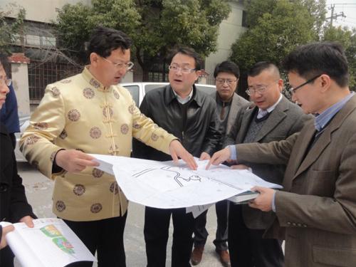 巨天中先生严谨细致地与企业领导查看地形布局图纸